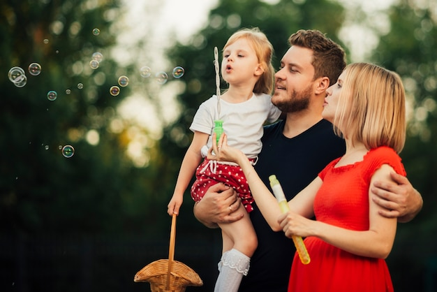 Familie blazende zeepbels in openlucht Gratis Foto