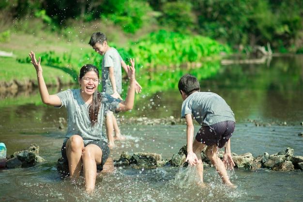 Familie die bij waterval in het bos samen gelukkige reist Premium Foto