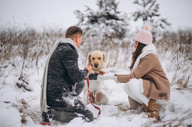 Familie die in de winterpark loopt met hun hond Gratis Foto