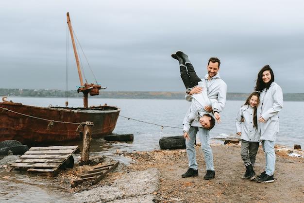 Familie die loopt en een pret dichtbij het overzees in regenjas heeft Premium Foto