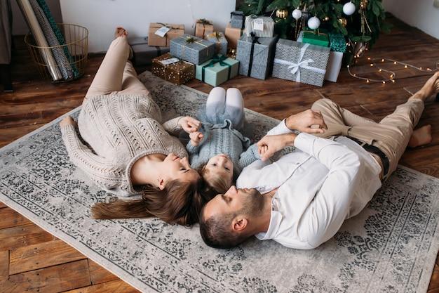 Familie die op de vloer thuis ligt. geschenkdozen en kerstboom Premium Foto