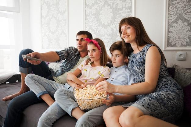 Familie die popcorn thuis eet tijdens het letten op televisie Gratis Foto