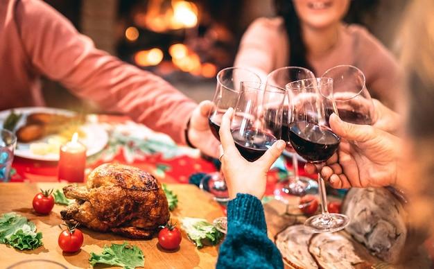 Familie die rode wijn roostert en pret heeft bij het avondmaalpartij van kerstmis Premium Foto