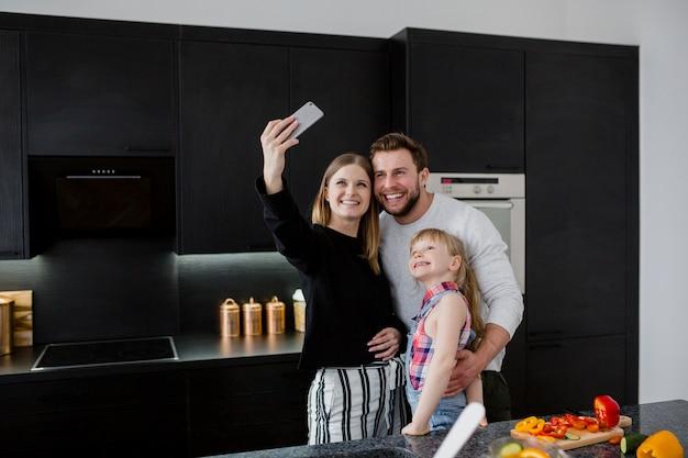 Familie die selfie in keuken nemen Gratis Foto