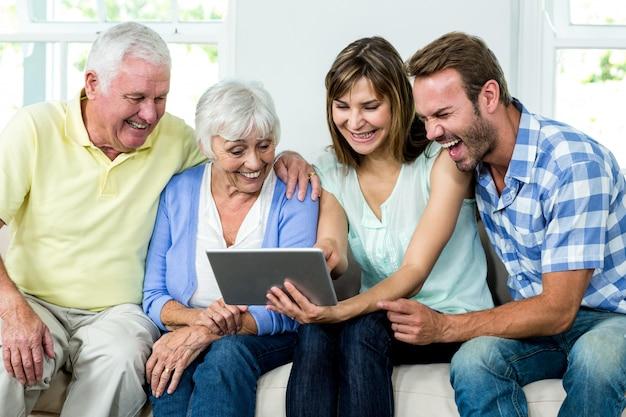 Familie die terwijl het kijken in digitale tablet lacht Premium Foto