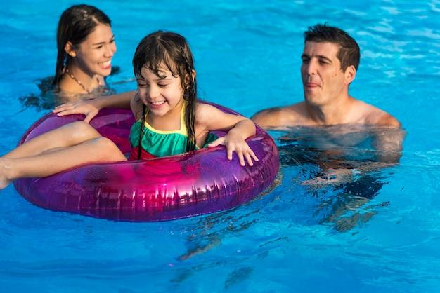 Familie die van een aardige dag bij de pool geniet Gratis Foto