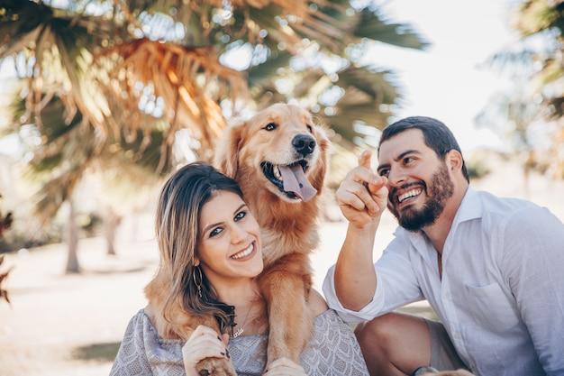 Familie die van een zonnige dag in het park met hun huisdier geniet. Premium Foto