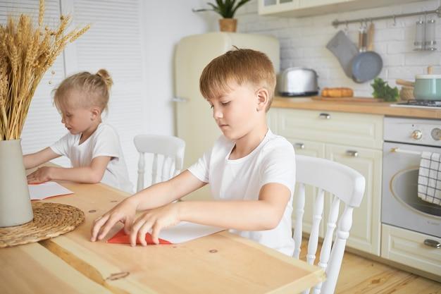 Familie en jeugdconcept. portret van twee mannelijke broers en zussen van de leerplichtige leeftijd zitten samen aan tafel in de keuken: blonde jongen huiswerk terwijl zijn oudere broer origami op voorgrond maken Gratis Foto