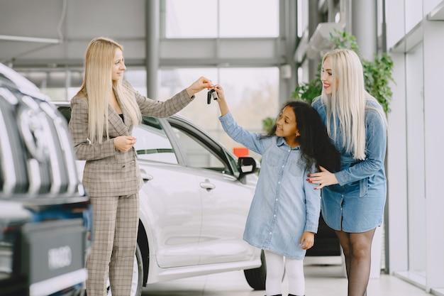 Familie in een autosalon. vrouw die de auto koopt. weinig afrikaans meisje met mther. manager met klanten. Gratis Foto