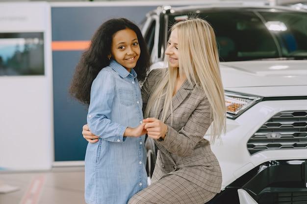 Familie in een autosalon. vrouw die de auto koopt. weinig afrikaans meisje met mther. Gratis Foto