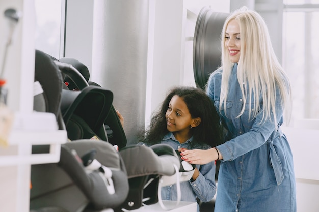 Familie in een autosalon. vrouw die de autostoel koopt. weinig afrikaans meisje met mther. Gratis Foto
