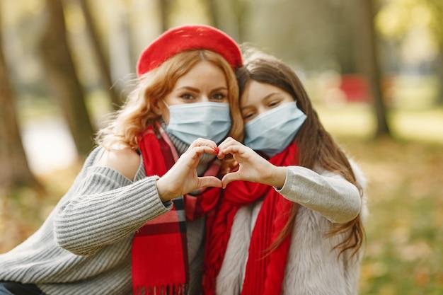 Familie in een herfstpark. coronavirus-thema. moeder met dochter. Gratis Foto