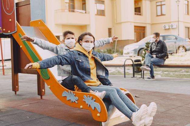 Familie in een masker staande op straat Gratis Foto