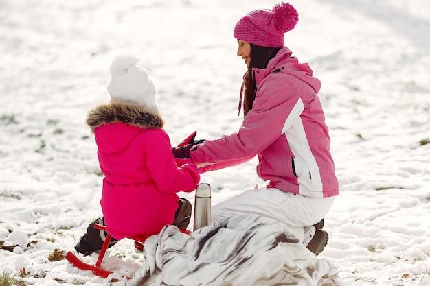 Familie in gebreide wintermutsen op familiekerstvakantie. vrouw en meisje in een park. mensen met thermoskan. Gratis Foto