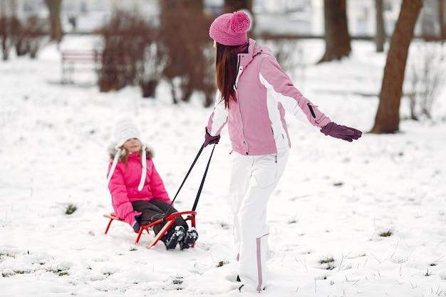Familie in gebreide wintermutsen op familiekerstvakantie. vrouw en meisje in een park. mensen spelen met slee. Gratis Foto