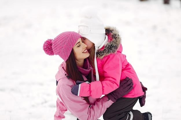 Familie in gebreide wintermutsen op familiekerstvakantie. vrouw en meisje in een park. mensen spelen. Gratis Foto