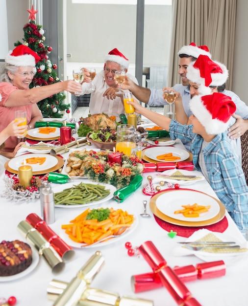 Familie in santahoeden die wijnglazen roosteren bij eettafel Premium Foto