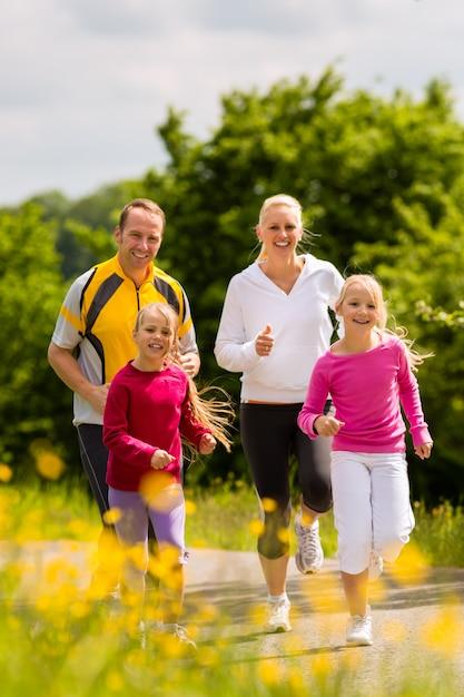 Familie joggen voor sport buitenshuis met de kinderen op zomerdag Premium Foto