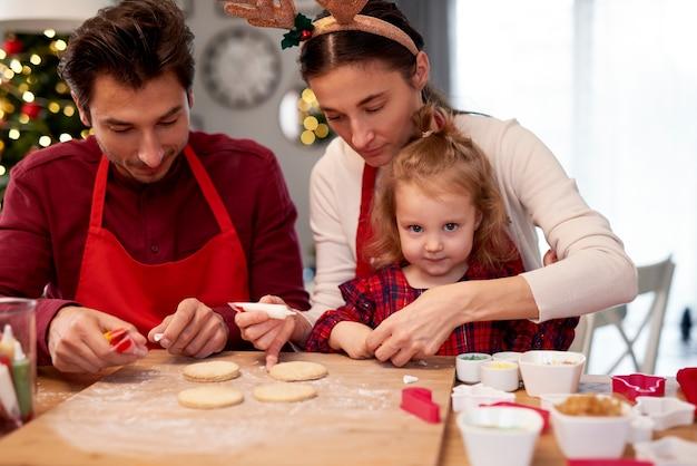 Familie kerstkoekjes in de keuken versieren Gratis Foto
