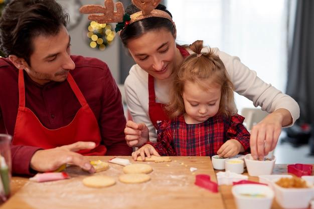 Familie kerstkoekjes samen in de keuken versieren Gratis Foto