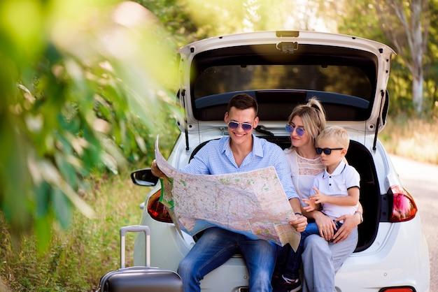 Familie klaar om te reizen en kies een plaats op de kaart waar naartoe te gaan Premium Foto