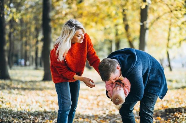 Familie met baby dochter die in een de herfstpark loopt Gratis Foto