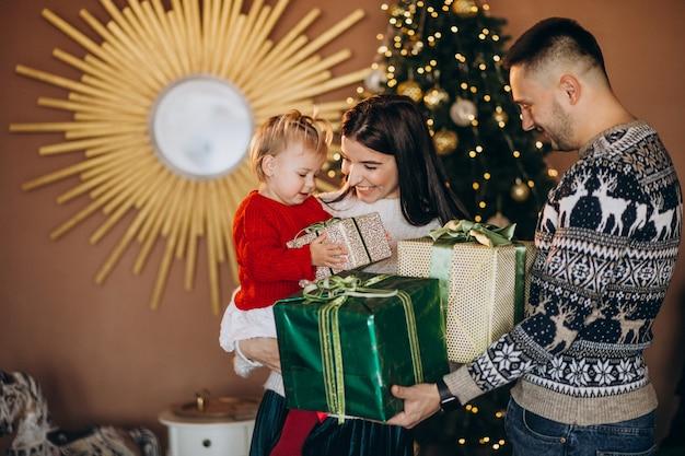 Familie met dochtertje door kerstboom uitpakken geschenkdoos Gratis Foto