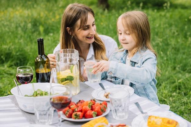 Familie met een picknick in de natuur Gratis Foto