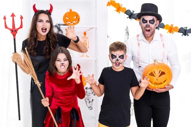 Familie met geschilderde gezichten die voor halloween stellen Gratis Foto
