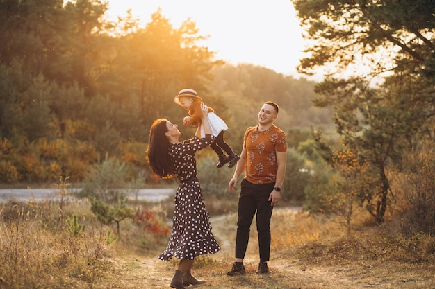 Familie met hun kleine dochter in een herfst veld Gratis Foto