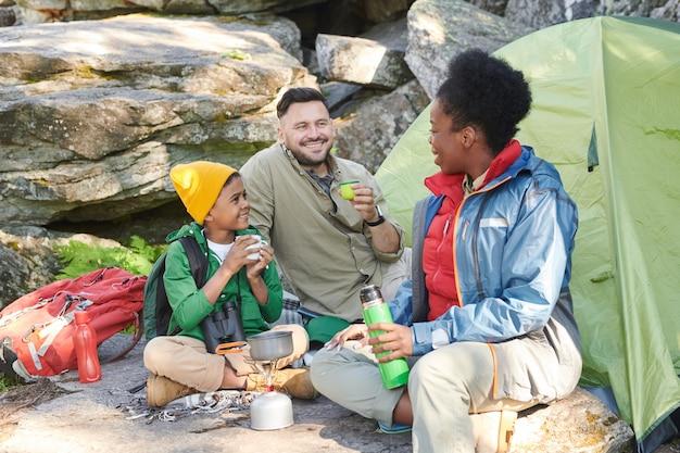 Familie met hun zoon die in de natuur met elkaar zitten praten en hete thee drinken tijdens hun reis Premium Foto