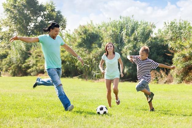 Familie met tiener spelen in voetbal Gratis Foto