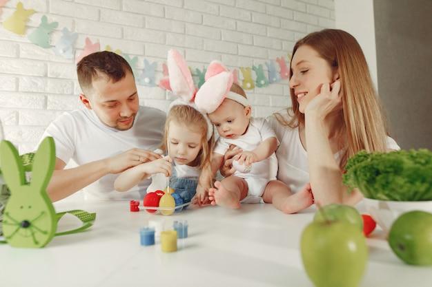 Familie met twee jonge geitjes in een keuken die aan pasen voorbereidingen treft Gratis Foto