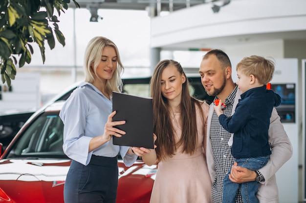 Familie met zoon die een auto in een autotoonzaal kiest Gratis Foto