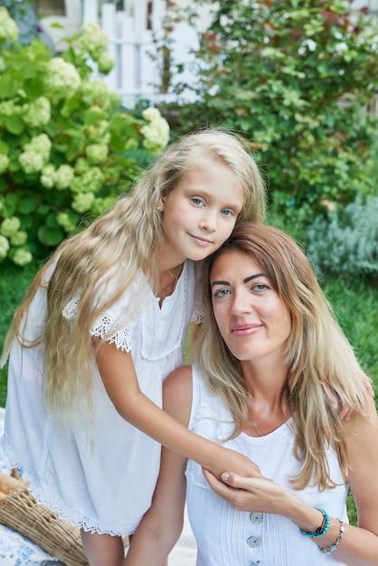 Familie moeder en dochter in de tuin in de zomer op een picknickrust Premium Foto
