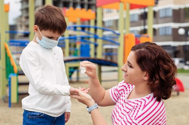 Familie moeder en zoon op de speelplaats. het kind draagt een beschermend medisch masker tijdens een epidemisch coronair virus of griep. persoonlijke beschermingsmiddelen. moeder geeft hand antisepticum aan haar baby Premium Foto