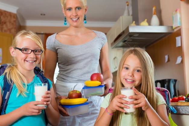 Familie, moeder maakt ontbijt voor school Premium Foto