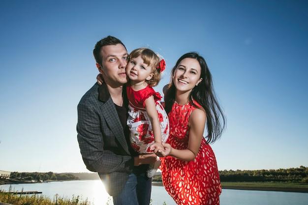 Familie, moeder, vader met de dochter gelukkig en prachtige zonsondergang lopen op de pier Premium Foto