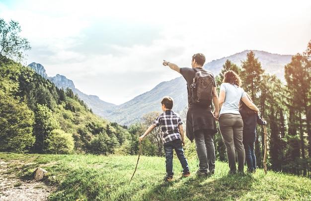 Familie op een groene weide die het bergpanorama bekijkt Premium Foto