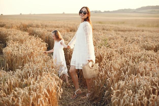 Familie op een zomergebied. sensuele foto. schattig klein meisje. vrouw in een witte jurk. Gratis Foto
