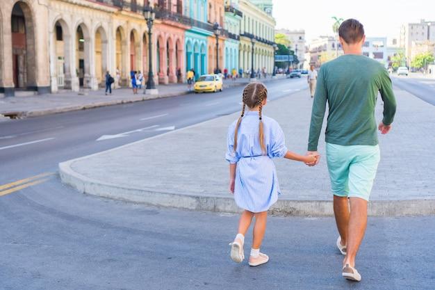 Familie op populair gebied in oud havana, cuba. klein kind en jonge vader buitenshuis op een straat van havana Premium Foto