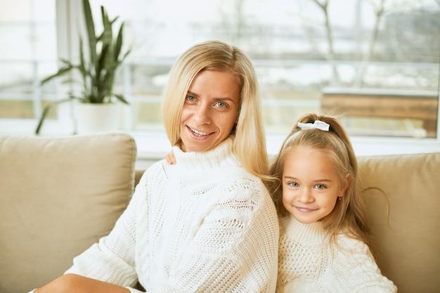 Familie, relaties, generatie, liefde en hechtingsconcept. stijlvolle jonge europese moeder met rechte lange haren glimlachend ontspannen op comfortabele bank, naast haar schattige dochter Gratis Foto