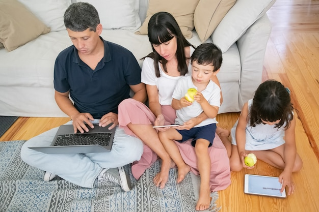 Familie samen genieten van vrije tijd, digitale gadgets gebruiken en verse appels eten in appartement. Gratis Foto