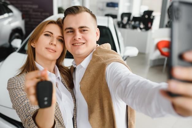 Familie selfie in dealer. gelukkig jong koppel kiest en koopt een nieuwe auto voor het gezin. Premium Foto