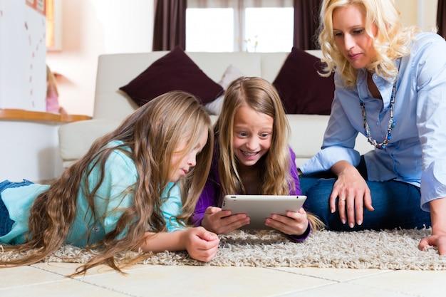 Familie spelen met tabletcomputer thuis Premium Foto
