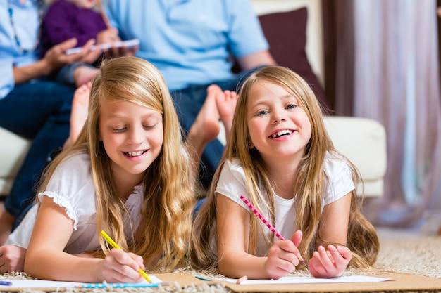 Familie thuis, de kinderen die op vloer kleuren Premium Foto