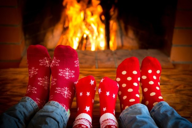 Familie thuis ontspannen. voeten in kerstsokken bij open haard. winter vakantie concept Premium Foto