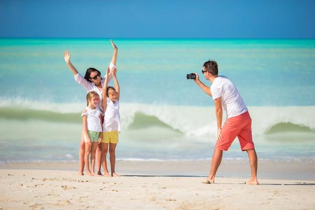 Familie van vier die een selfiefoto nemen op hun strandvakantie. familie strandvakantie Premium Foto
