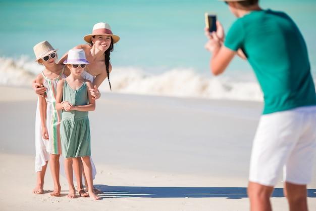 Familie van vier die een selfiefoto nemen op hun strandvakantie. Premium Foto