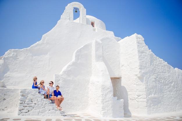 Familie van vier op de trappen van paraportiani-kerk op het eiland mykonos, in griekenland Premium Foto